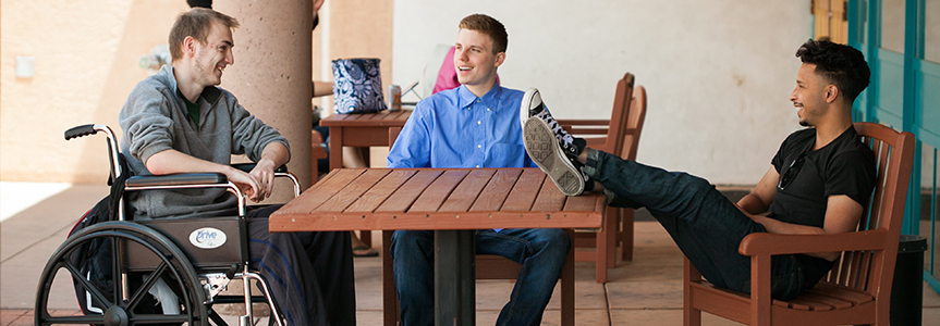 3 students outside at table
