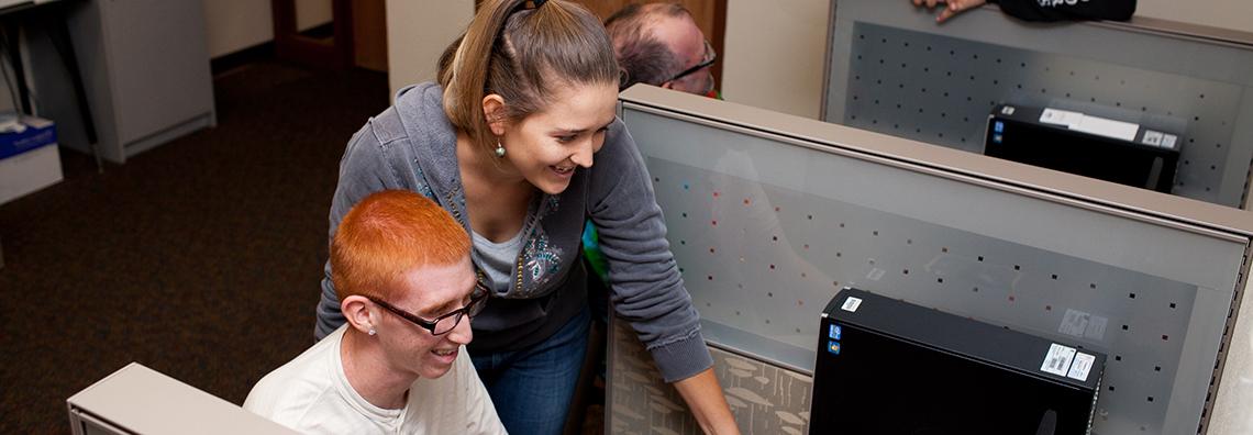 girl over boys shoulder at computer