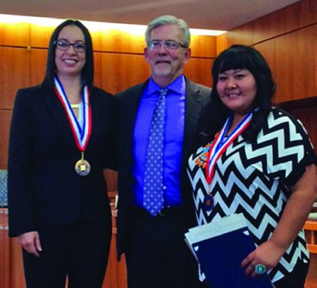 "President Randy Grissom congratulates Mayala ""Maya"" Gomez de Gutierrez, left, and Avadana Garcia, right, at recognition ceremonies at the Roundhouse on February 4."