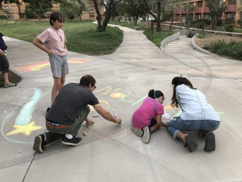 Kids and adults have fun making chalk art at the Aug. 17 event.