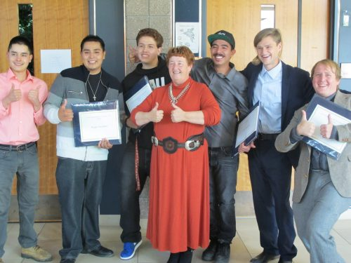 EPA job-training instructor Janet Kerley celebrates with the graduates after the ceremony. Left to right: Rudy Garcia, Kegan (Wade) Gachupin, Anthony Martinez, instructor Janet Kerley (in front), Nico Randall, Bennett Campbell and William Wolfe.