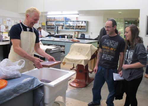 Printmaking instructor Gordon Fluke demonstrates papermaking to Jason Portillos and his daughter Jade, a senior at Los Alamos High School.