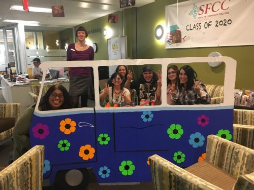 Having fun at Swingin' Sixties: In the background at desk is student worker Jake Quintana. Left to right: Melba Ramos, Emily Powell, Tammy Duran, Gregoria Cavasoz, Gerard Martinez y Valencia, Elizabeth Solis and Danielle Gonzales.