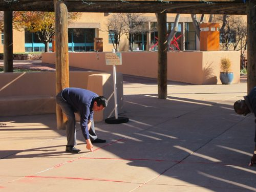 Marvin Galbadon, SFCC data technician, meticulously places red sand for the art installation.
