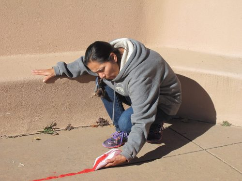 Student Tara Duran, president of the campus Native American Club, reflects about the serious nature of the Red Sand installation as she places the sand.