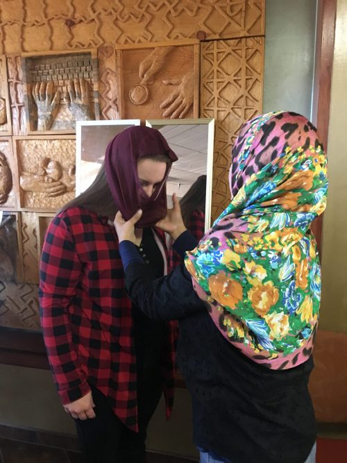 Dr. Aamna Nayaar helps a student try on a hijab.