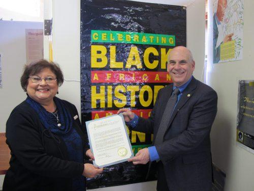 Interim President Cecilia Cervantes, Ph.D. and Santa Fe Mayor Alan Webber display the proclamation for Black History Month.
