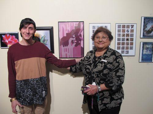 SFCC's interim president Cecilia Cervantes congratulates Media Arts student Jesus Gallegos as they stand next to his artwork.