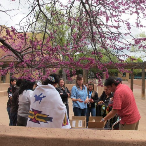 Participants gather to collect the red sand to pour between the cracks in the Courtyard.