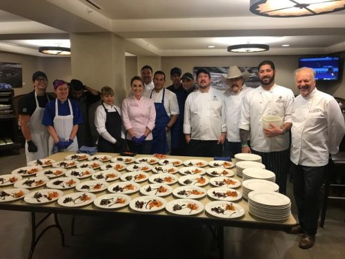 At far left, SFCC Culinary Arts students Joshua Rodriguez and Emma Keener gather with the chefs to admire their dessert molé appetizer with eldible flowers.