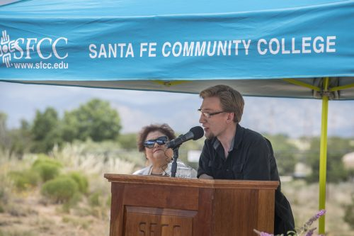 Interim president Cecilia Cervantes, Ph.D., looks on proudly as one of SFCC's automotive technology students, Nathan Sindelar, speaks to the crowd.