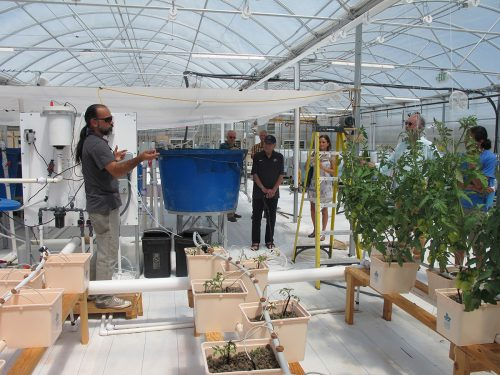 SFCC's greenhouse technician and instructor for Controlled Environmental Agriculture Pedro Casas Cordero (at far left) talks about the college's aquaculture, hydroponics and greenhouse classes.