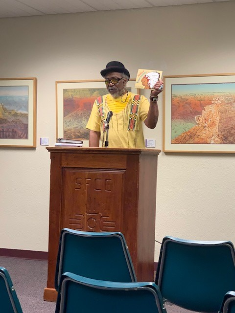 Tyrone Wright participated in SOW reading in the library.  He holds up a painting by cartoonist Ricardo Caté.