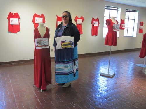 SFCC Associate Dean Brooke Gondara stands next to the red dress representing her murdered great-grandmother Elizabeth Beaverheart Akins Plenty Chief, Northern Cheyenne Nation, Montana.