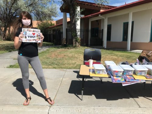 Pre-K teacher Abrianna Martinez holds a We Love You sign as parents arrive to pick-up their kits.