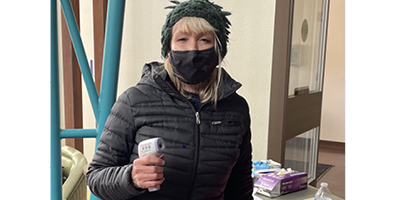 Linda Cassel, director of Art on Campus, took temperatures as part of the screening of participants at the April celebration and volunteer event.